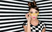 stock photo of hair bow  - Attractive surprised young woman wearing glasses on checkered background - JPG