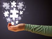 Woman holding shining puzzle pieces in her hand