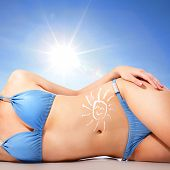 foto of sun tan lotion  - Attractive young woman body at the beach with sun shaped cream  - JPG