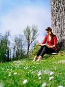 Young Woman Reading And Enjoying Spring