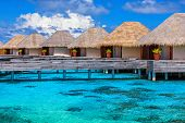 Luxury beach resort on Maldives, many cute bungalows standing on transparent water, Indian ocean, ro