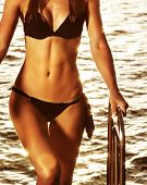 Supermodel on the beach, perfect slim body part, mild yellow sunset light, healthy lifestyle, summer