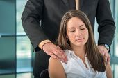 Business woman getting a backrub from colleague in office