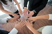 Group of hands joining together in office environment