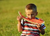 Kid eating water melon on meadow