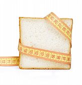 Piece of bread grasped by measuring tape isolated on white
