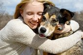 stock photo of shepherd  - a loving and candid portrait of a happy woman hugging her large German Shepherd dog - JPG
