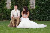 stock photo of redneck  - Hillbilly hipster vintage style bride and groom outside church after wedding ceremony - JPG
