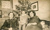 SCHWEINHEIM, GERMANY, DECEMBER 25, 1955: Vintage photo of parents with little daughter near Christma