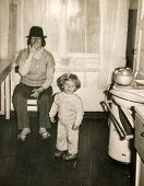 LODZ, POLAND, CIRCA 1950's: Vintage photo of mother with little child in kitchen