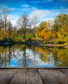 Picturesque autumn landscape of river and bright trees and bushes and wood pier