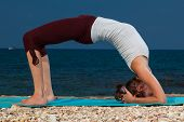 young woman yoga exercises on the beach