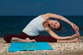 Young woman yoga exercises on a beach
