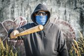 Man holds a baseball bat forward on a wall background