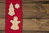 stock photo of ginger bread  - A Ginger Bread Woman Christmas Tree and Star on Red Drapery on Wooden Background with Copy Space - JPG