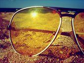 sunglasses on sand near a sea