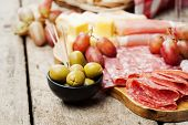 image of charcuterie  - Charcuterie assortment and olives on wooden background - JPG