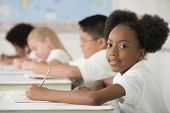Multi-ethnic children writing at desks in classroom