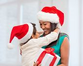 holidays, presents, christmas, x-mas concept - happy mother and child girl in santa helper hats with
