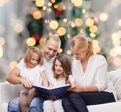 family, childhood, holidays and people - smiling mother, father and little girls reading book over living room and christmas tree lights background