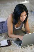 Asian woman using laptop on floor