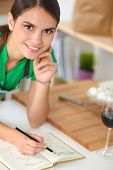 Happy beautiful woman standing in her kitchen writing on a note