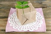 Natural style handcrafted gift box with fresh leaves and rustic twine, on napkin, on wooden background