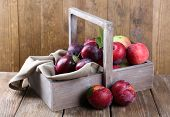 Sweet plums in wooden basket on table on brown background