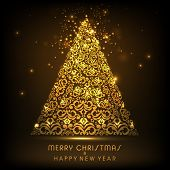 Beautiful floral design decorated golden Xmas tree on brown background for Merry Christmas and Happy New Year celebrations.