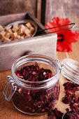 Dried hibiscus tea in glass jar, fresh hibiscus flower and brown sugar in box, on wooden background