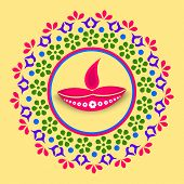Stylish colorfull rangoli with illuminated oil lit lamp for diwali celebration on yellow background.
