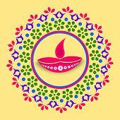 picture of rangoli  - Stylish colorfull rangoli with illuminated oil lit lamp for diwali celebration on yellow background - JPG