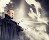 stock photo of priest  - Exorcist priest fights a demon in a dark room - JPG