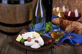 Supper consisting of Camembert and Brie cheese, honey, wine and grapes on napkin in basket and wine