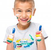Portrait of a cute boy playing with paints and showing thumb up sign using both hands, isolated over white