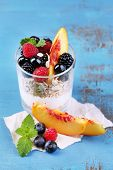 Healthy breakfast - yogurt with  fresh fruit, berries and muesli served in glass on color wooden background