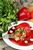 Prepared stuffed pepper with tomato sauce on plate, on wooden background