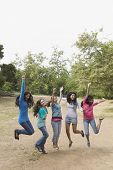 Hispanic teenaged girls cheering and jumping