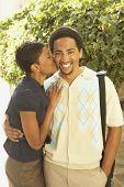 African American woman kissing boyfriend on cheek