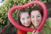 Hispanic mother and daughter holding heart-shaped balloon