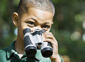 Mixed Race boy holding binoculars
