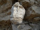 Stone face on the rocks abstract background