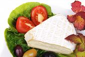 aged camembert cheese on green salad in white platter with olives and tomato isolated over white background