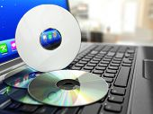 Software CD on laptop keyboard. Compact disks. 3d