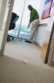 African businessman playing golf in office