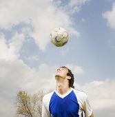 Native American male soccer player bouncing ball on head