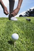 African man on golf course tying shoe