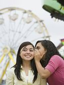 Multi-ethnic teenaged girls telling secret