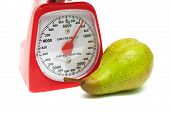 Ripe Pear And Kitchen Scales Close Up On A White Background