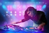 picture of disc jockey  - Pretty young disc jockey mixing music on turntables on stage with lights and stroboscopes - JPG